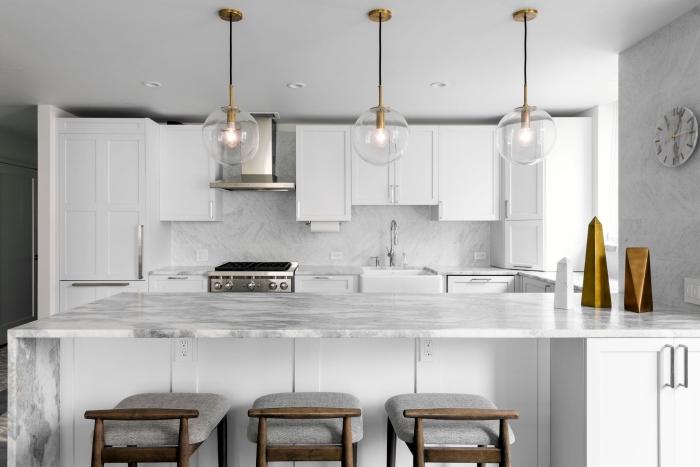cuisine blanche et stylée aux murs et crédence à effet marbre, déco de cuisine avec îlot, exemple cuisine blanche avec accessoires or