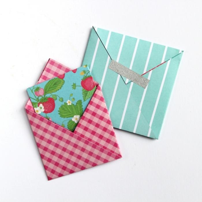 deux modèles d'origami enveloppe en version mini fabriqués en papier origami motif rayures et carreaux, enveloppe diy en origami fermée avec un bout de washi tape