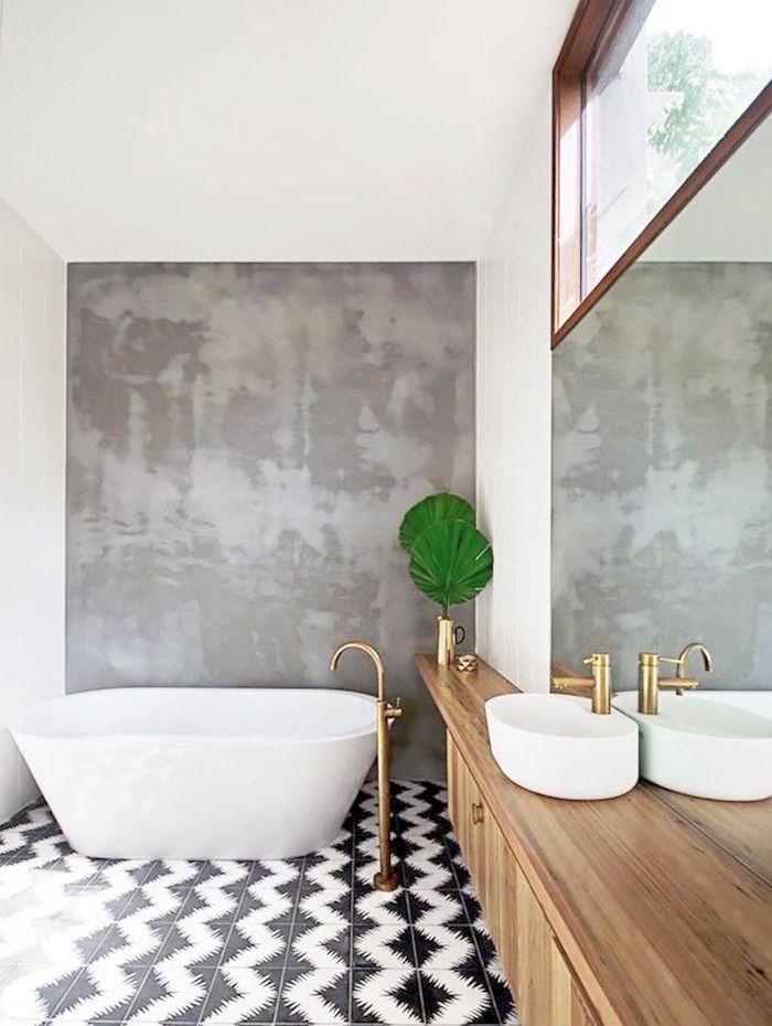 idée déco de salle de bain ouverte avec baignoire ilot et mini vasque de lavabo sur meuble en bois et robinetterie or avec sol carrelage noir et blanc et mur gris en béton ciré