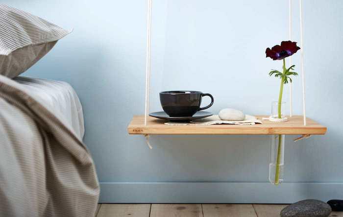 idée simple pour faire une table de chevet suspendue en planche de bois à découper, tasse de café et soliflore sur fond mur bleu ciel