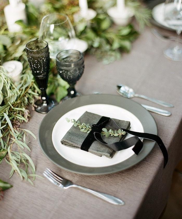 simple idee de pliage de serviette en carré avec décoration plante verte et ruban noir sur nappe grise, centre de table végétation verte et multitude de bougeoirs, deco mariage champetre