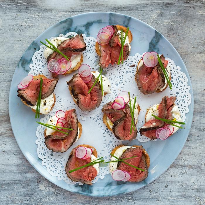 amuse bouche facile et rapide, viande de boeuf sur tranche de baguette, brins de romarin et fromage, assiette ronde