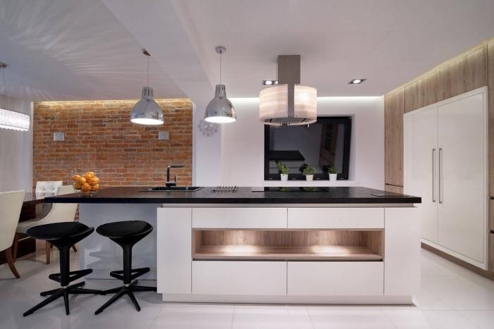 design intérieur moderne dans une large cuisine avec coin repas, modèle de cuisine avec îlot central, exemple mur en briques rouges dans une cuisine équipée