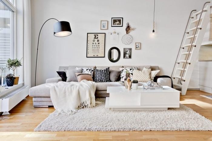 intérieur hygge deco cocooning de style scandinave, petit salon chaleureux avec grand canapé moelleux et un parquet clair qui apporte de la luminosité