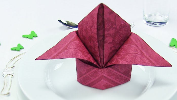 exemple original de pliage de serviette en papier couleur framboise dans assiette blanche, deco mariage élégante
