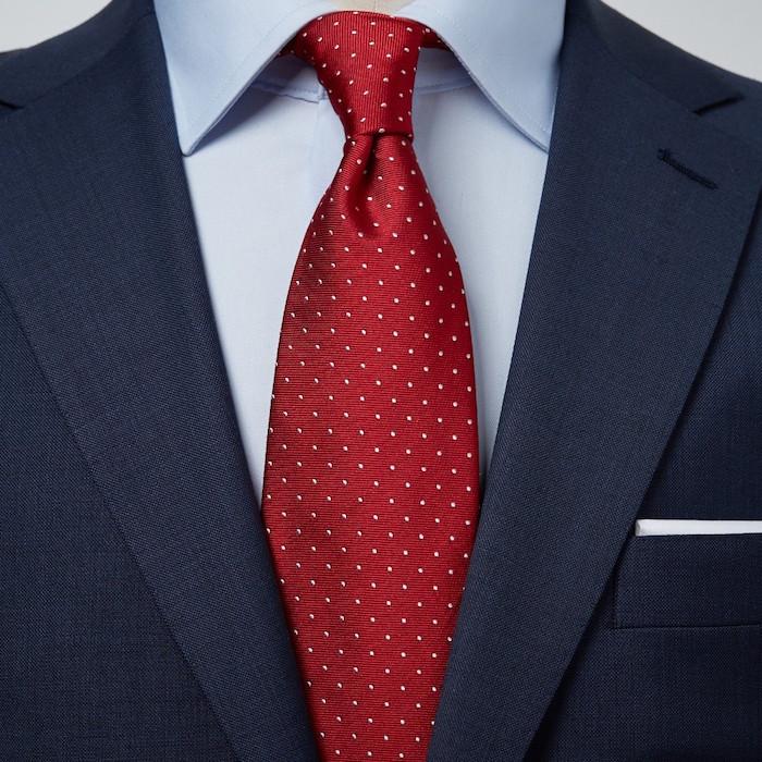 photo de Cravate classique rouge bordeaux à pois blanc en noeud windsor sur chemise bleu clair et costume marine