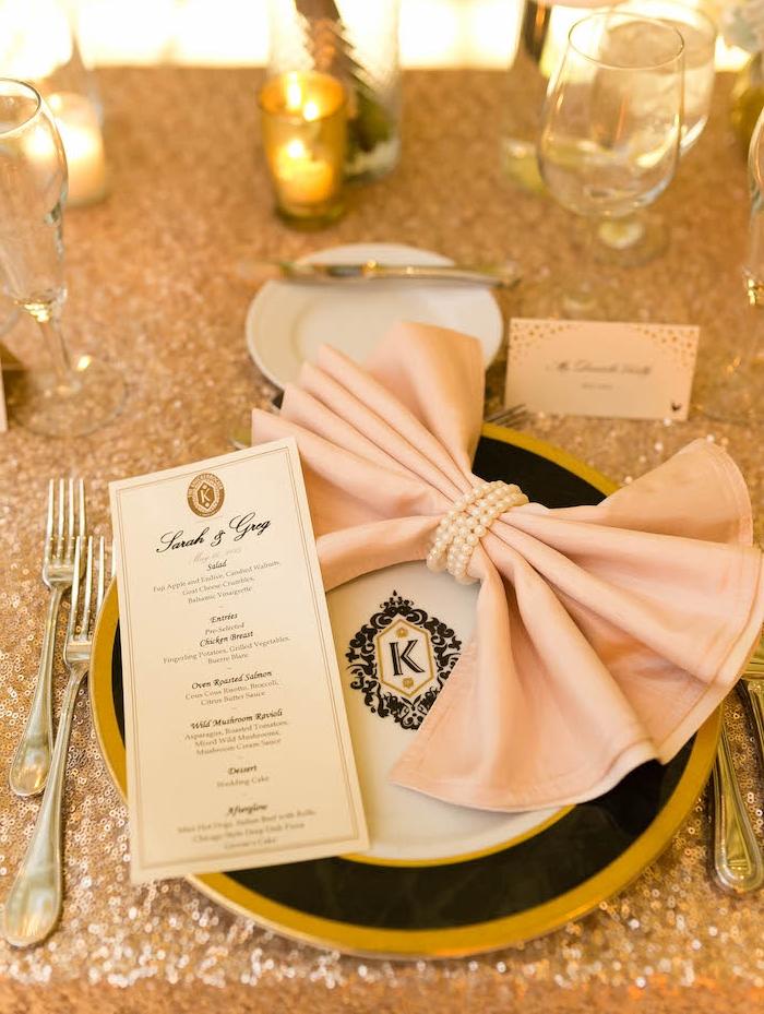 comment créer une déco mariage de style glamour avec nappe en paillettes dorées, assiette noir et or à emblème, pliage serviette en noeud de papillon décoré de perles blanches