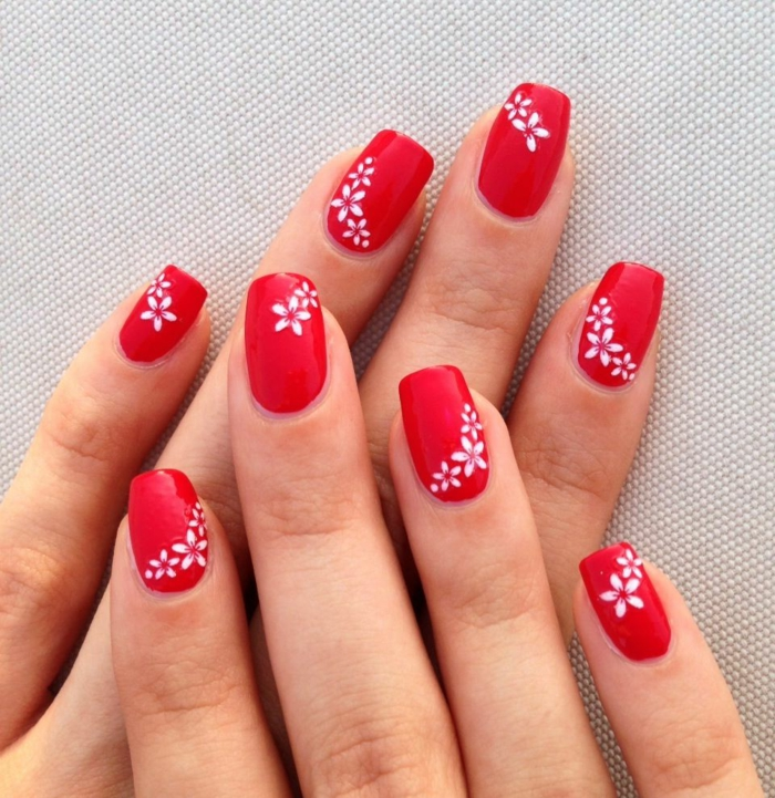 ongles carrés arrondis aux motifs floraux, vernis rouge vif, design de manucure pour des mains fines