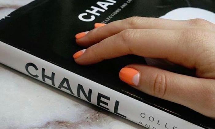 manucure demi lune en orange et blanc, ongles carrés, livre en noir et blanc