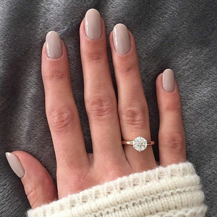 ongles gris clair, bague et pull d'hiver blanc, forme d'ongle ovale, ongles mi-longs