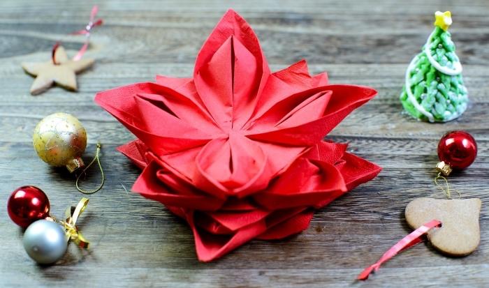 technique de pliage serviette pour noel, idée comment plier une serviette en forme florale, art origami avec serviette rouge