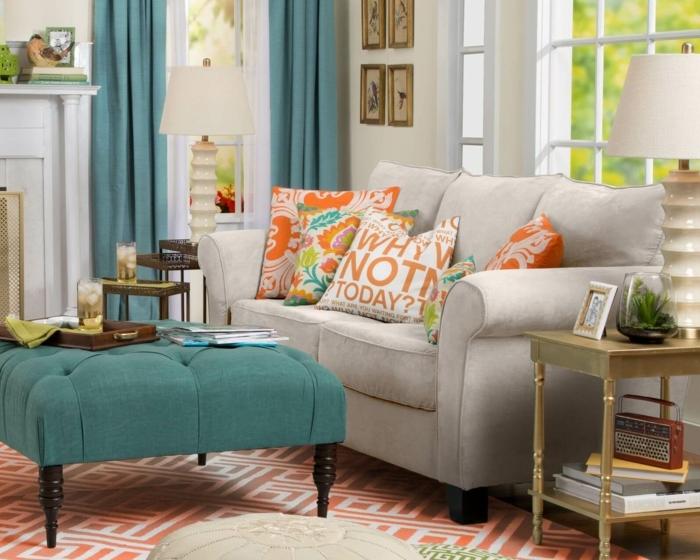 tapis aux motifs géométriques, ottomane bleue, coussins avec scripts, sofa gris, table basse de deux niveaux, rideaux bleus