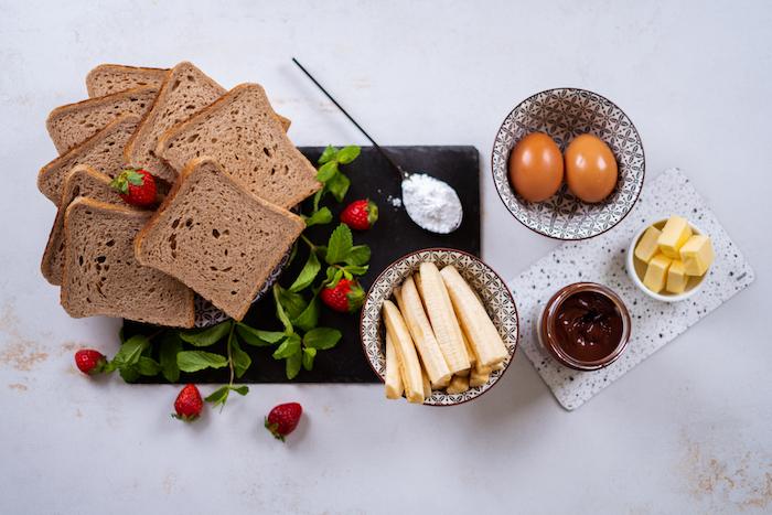 ingredients necessaires pour faire roulé pain de mie avec des tranches de pain, batons de banane, oeufs, chocolat à tartiner nutella, beurre