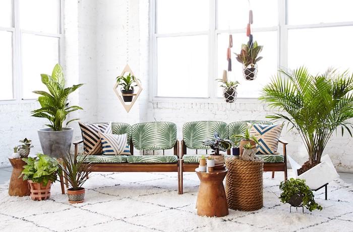 deco salon tropical avec canapé bois, dossier et coussins à imprimé palmier, plusieurs pots de fleurs suspendus et posés, mur de briques blanches, tapis blanc