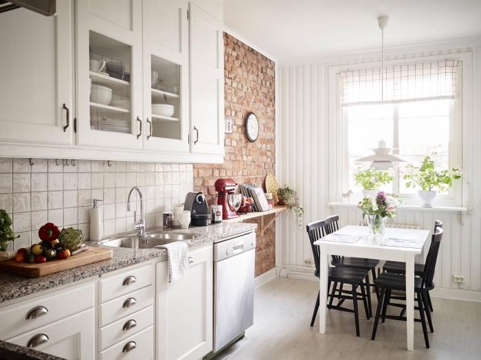comment décorer un mur dans une cuisine blanche, idée crédence de cuisine avec carrelage blanc, mur en briques rouges intérieur
