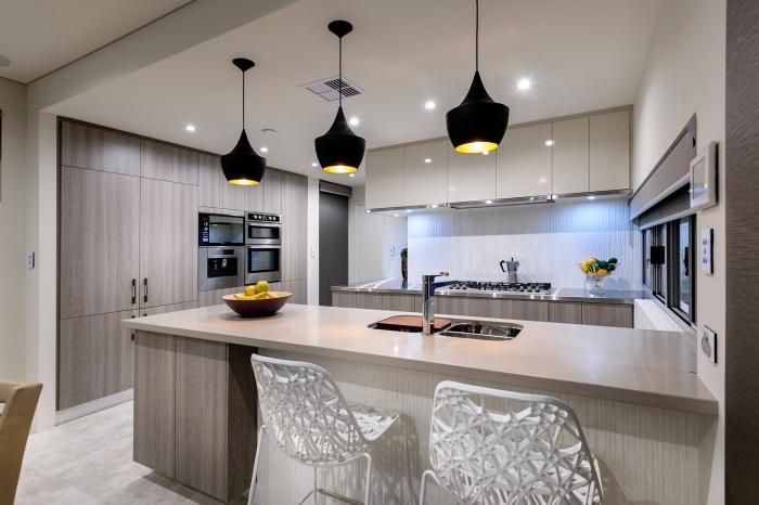 design intérieur tendance moderne dans une cuisine blanc et bois, exemple agencement cuisine avec îlot et lampes suspendues