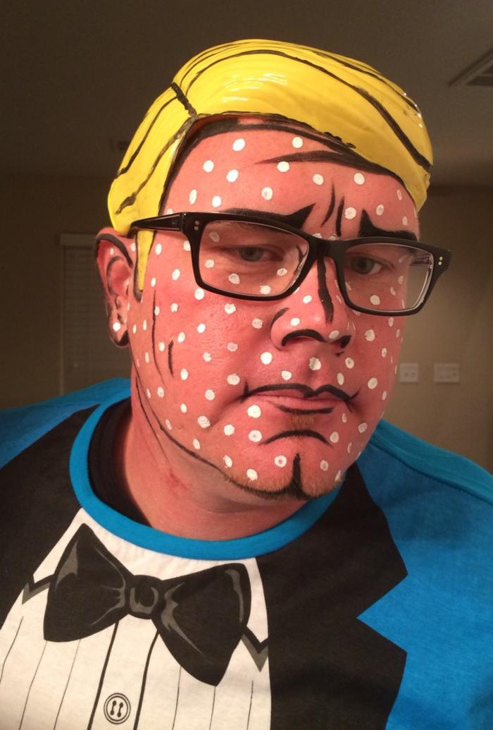 peinture visage rose à pois blancs, lunettes de vue, perruque en plastique jaune, pèlerine bleue