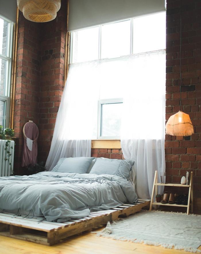 sommier en palette avec matelas et linge maison gris, rangement chaussures et table de nuit bois clair, mur de briques, style industriel moderne