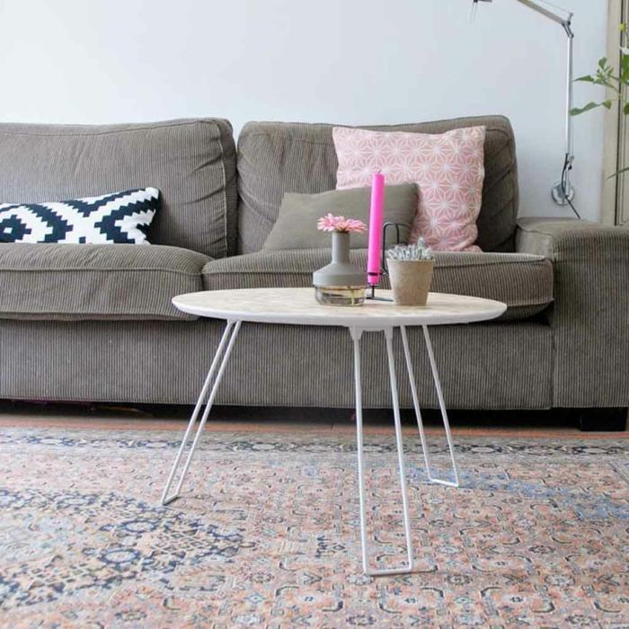 table basse ronde, bougie rose, vase gris avec petite fleur, tapis persan aux couleurs pastels, sofa gris, coussins décoratifs, peinture murale grise