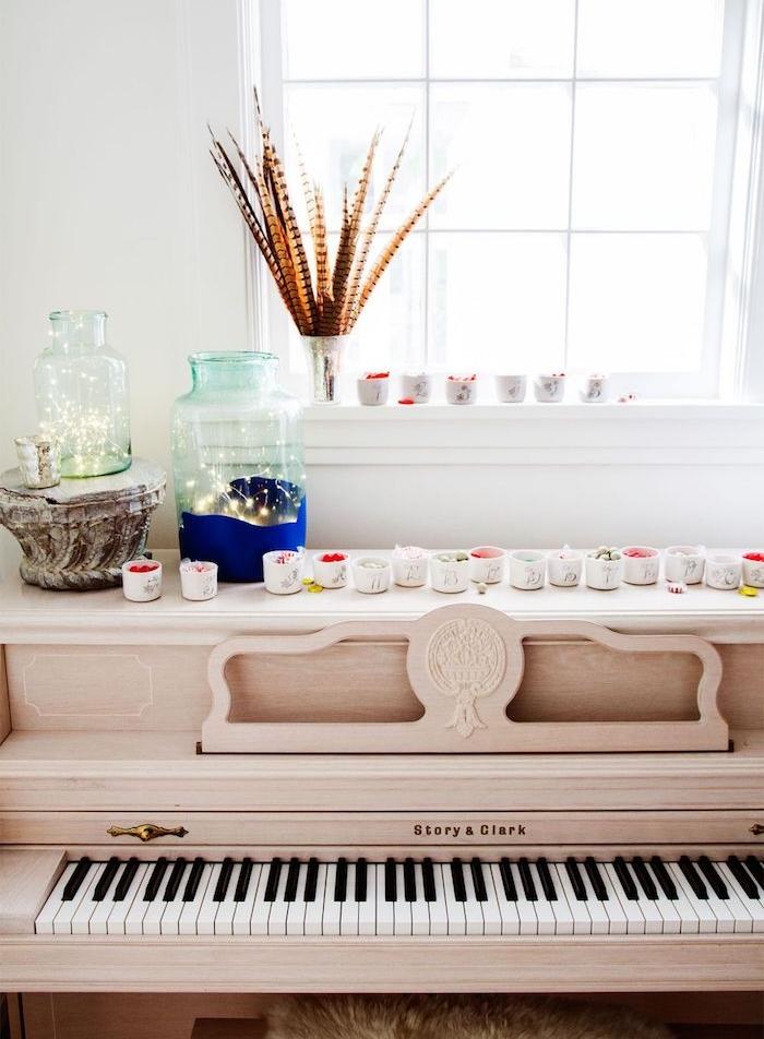 calendrier de l avent maison, petites coupelles remplies de gourmandises sur une piano, bocal avec guirlandes lumineuses décoratif