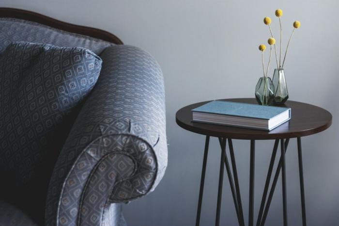 table d'appoint ronde, vases angulaires, plantes décoratives jaunes, sofa vintage et mur gris