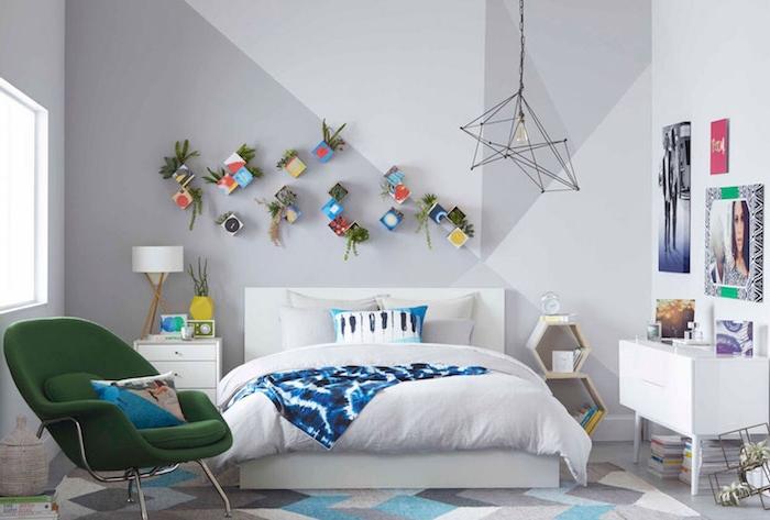 modele de chambre adulte moderne en gris et blanc avec fauteuil verte et des plantes vertes dans boites de carton rangées sur un mur gris et blanc, suspension originale, deco portraits et art murale