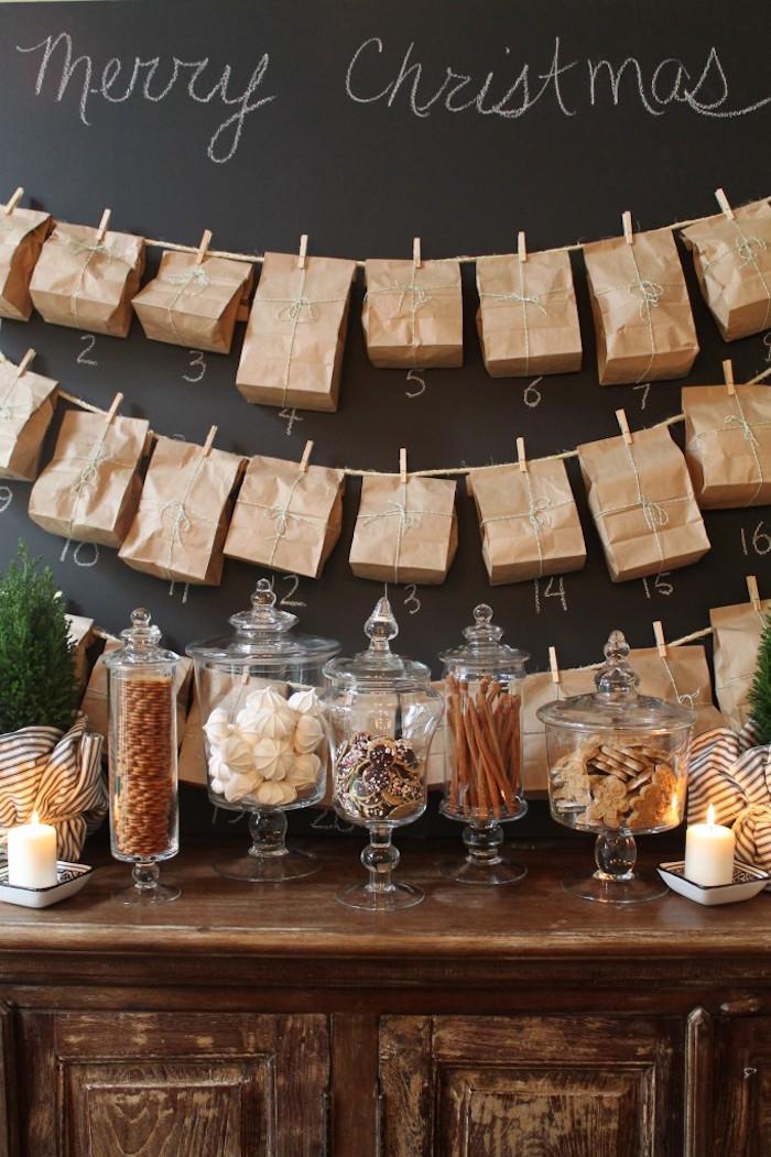 tableau noir peinture à la craie avec des sachets papier kraft suspendus sur des fils à des pinces à linge de bois, candy bar de noel avec gourmandises dans pots en verre