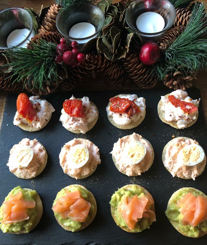 tomates séchées, oeufs, avocats tartinés sur de petites bouchées de pain, couronne de noel en branches de pin et pommes de pin