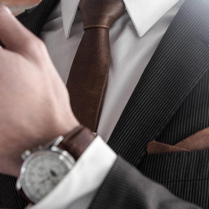 photo de cravate en cuir marron assortie à montre et pochette sur smoking noir gris rayé et chemise blanche