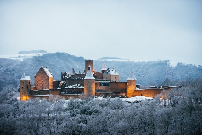 joli paysage d'hiver dans les montagnes avec une forteresse aux lumières allumées, idée fond d'écran noel ou hiver