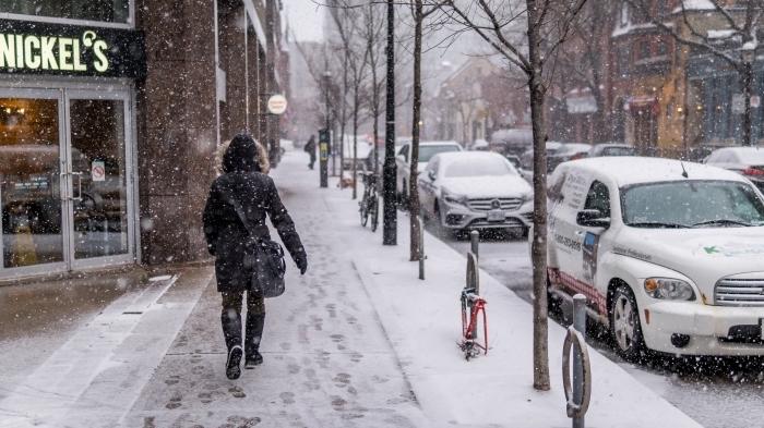 idée pour fond d'écran original pc, paysage d'hiver au centre ville, photo de flocons de neige qui tombent et femme qui marche dans une ville enneigée
