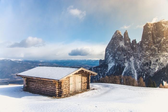 joli paysage de noel ou d'hiver, photo de cabane de bois sur un colin dans les montagnes enneigées, image lever du soleil en hiver