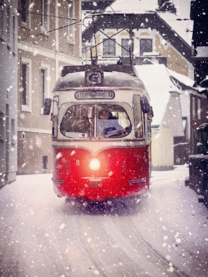 idée fond d écran noel, photo de tram rouge dans un village en hiver, photo de la neige qui tombe dans un village