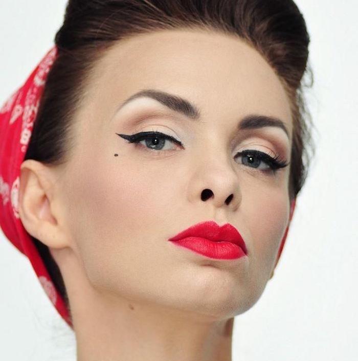 femme pin up retro avec bandana rouge dans les cheveux, coiffure année 50 vintage et maquillage pinup eyeliner noir et lipstick rouge vif