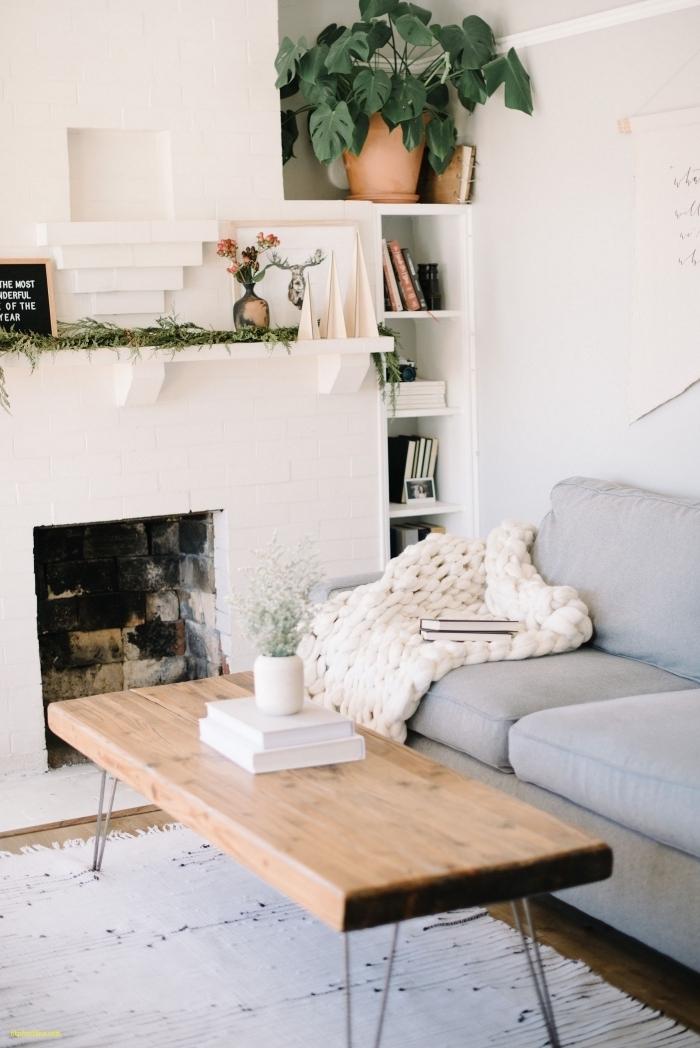 coin salon scandinave aux accents natures avec un canapé gris accessoirisé d'un plaid grosse maille blanc, installé près de la cheminée à foyer ouvert,