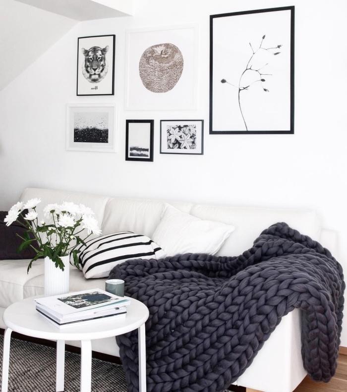 petit salon noir et blanc de style scandinave épuré et minimaliste d'esprit cocooning traditionnel pour les pays du nord, deco cocooning et personnalisée avec une galerie murale monochrome et un canapé blanc accessoirisé d'un plaid grosse maille gris