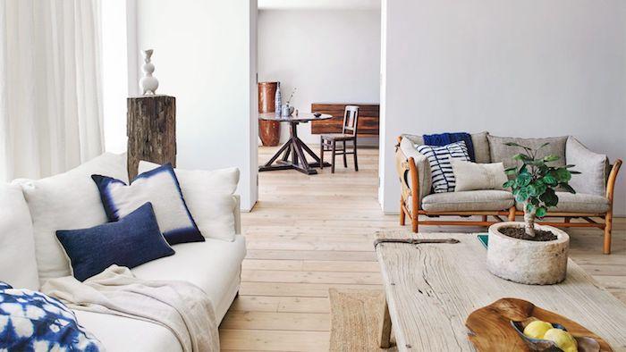 deco salon rustique moderne avec un bonsai sur une table basse bois brut, canapé blanc cassé, coussins blanc et bleu marine, parquet bois brut