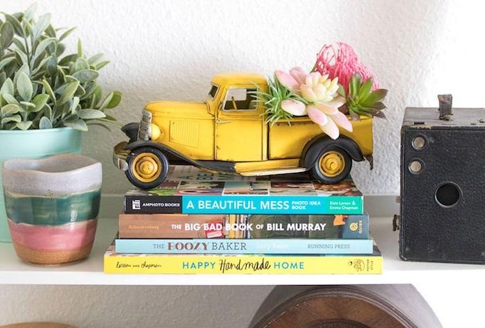 succulents plantés dans un joeut voiture jaune et autre plante verte à côté,, pile de livres, plantes grasses d intérieur