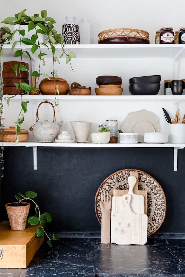 étagères ouvertes blanches avec des ustensiles de cuisine exposés, crédence noire et plan de travail cuisine marbre noir, deco africaine avec plante tombante intérieur