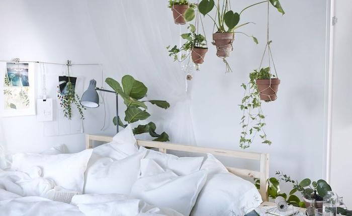 idee deco chambre blanche avec des pots de fleurs suspendus au dessus d un lit bois avec linge de lit blanc, plante d appartement
