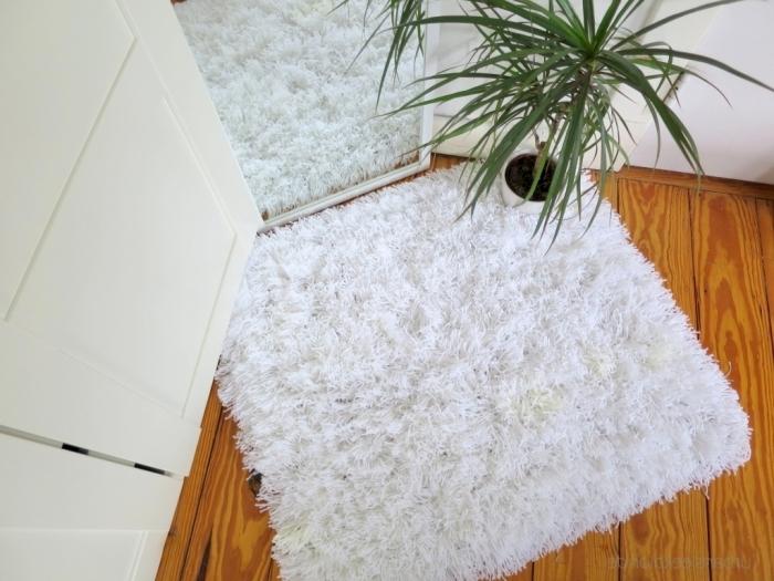 ambiance cocooning dans une chambre blanche au parquet bois avec objet déco fait main, modèle tapis diy en fausse fourrure