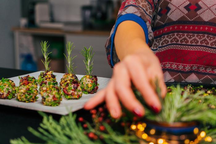 planter un brin de romarin frais dans une boule de fromage recouverte de persil frais, canneberges et pistaches