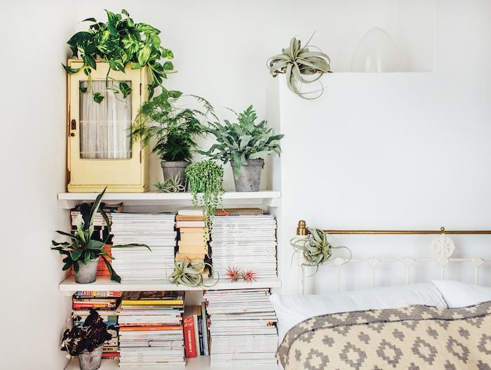 idee de lit metallique avec linge de lit blanc, gris et beige, étagères blanches avec livres et plantes vertes en pot, deco chambre nature