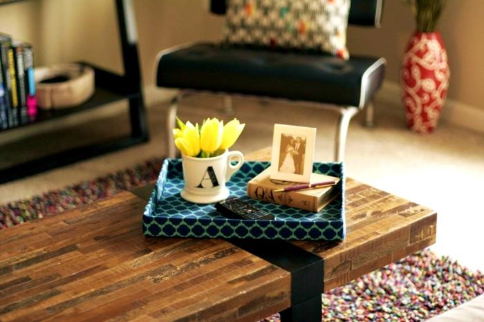 décoration pour table basse en bois, boîte bleue, tasse blanche, tulipes jaunes, vase aux motifs floraux