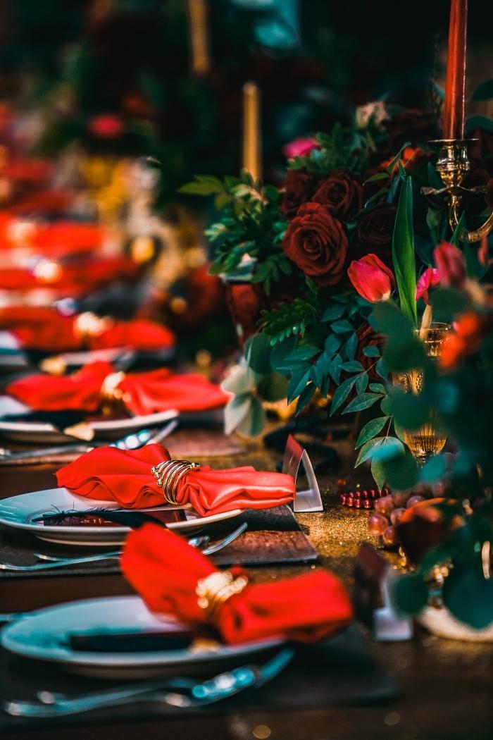 magnifique décoration de table de Noel avec bouquets de roses rouges et bougeoirs dorés, idée pliage serviette etoile ou papillon