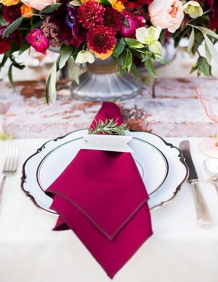 pliage serviette triangle, idee simple avec serviette tissu couleur bordeaux avec marque place écrit sur papier et anneau en brin de pin
