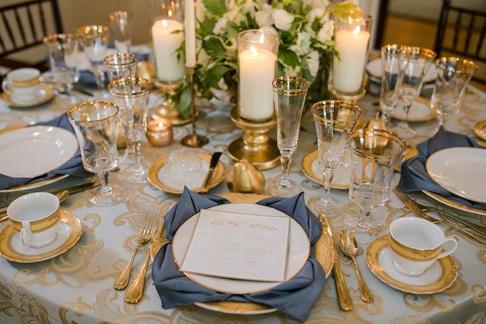 décoration élégante de mariage avec serviettes en tissu pliées en forme de fleur de lotus sous assiette, couverts, vaisselle et bougeoirs dorés