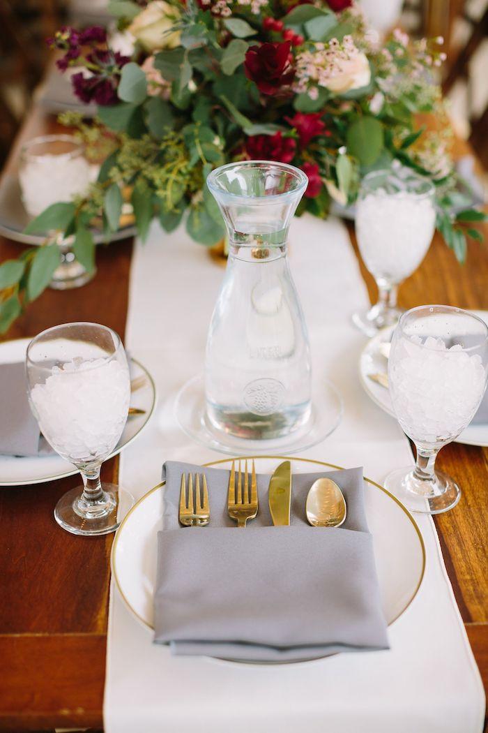 chemin de table blanc avec bouquet de fleurs champetre au centre sur table bois, assiette blanche avec pliage de serviette pour mariage pochette tissu