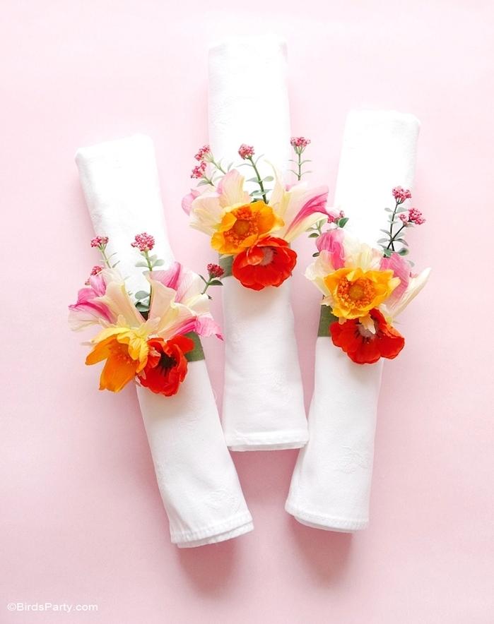 serviettes enroulées avec un anneau en bande de tissu décorée de fleurs artificielles colorées pour votre mariage theme floral