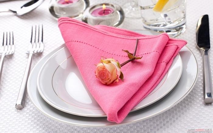idee simple de pliage de serviette facile en forme de triangle rose décoré de petite rose dans assiette, nappe blanche, bougies au centre